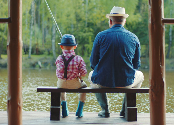 A grandpa and grandson are fishing together.